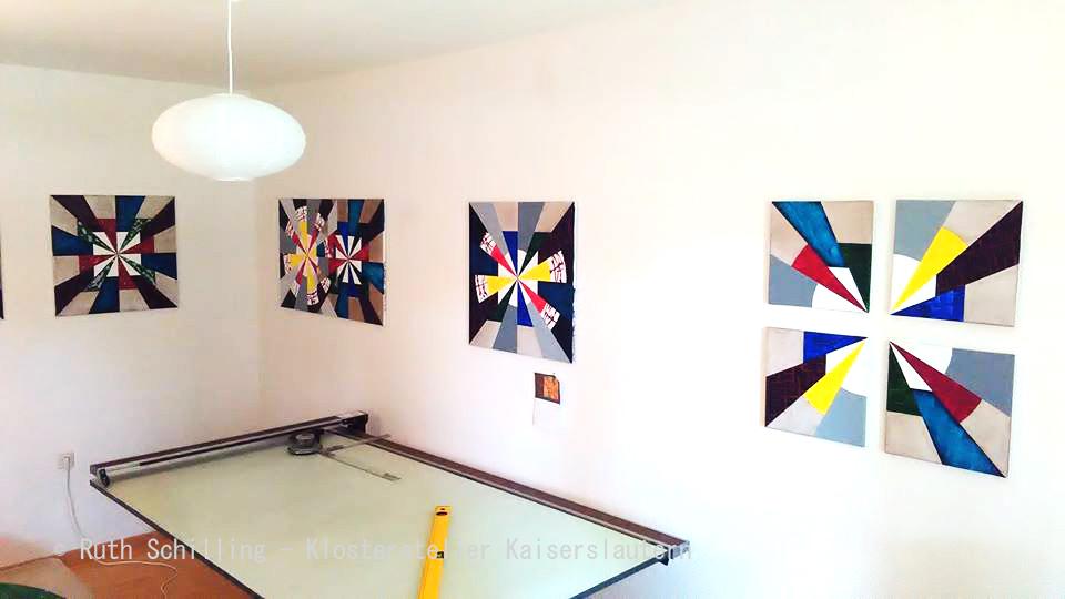 Hier ist mein Arbeitsplatz im Klosteratelier zu sehen, dieser besteht aus einem alten höhenverstellbaren Zeichentisch, Gemälde mit geometrischen Mustern sind an der Wand hängend zu sehen.